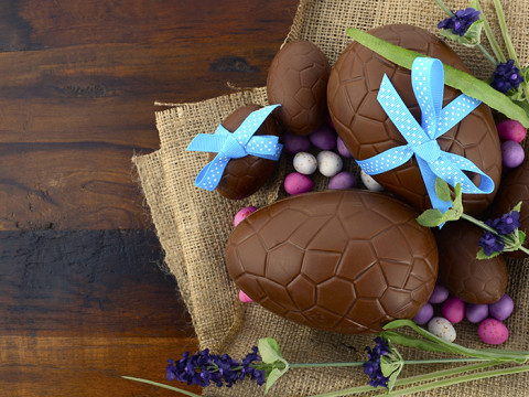 Happy Easter chocolate Easter eggs on dark wood country style table background.